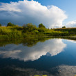Evening after rain at the bank of a small river with rain clouds on the background — Stock Photo