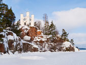 Winter landscape with chapel on the top of rocky island and froz — Stock Photo