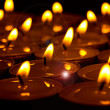 Group of burning round candles on black background — Stock Photo