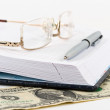 Opened notebook, metallic pen, gold spectacles and dollar note — Stock Photo