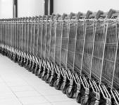 Row of empty shopping carts in big supermarket. Black and white — Stock Photo