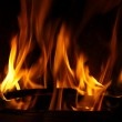 Fire in a fireplace, fire flames on a black background — Stock Photo #22452055