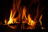 Fire in a fireplace, fire flames on a black background — Stock Photo