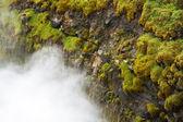 Felsen mit grünem Gras und sinkende Wasserdampf — Stockfoto