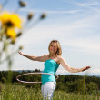 Blond mature woman exercises with hula hoop — Stock Photo