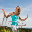 Blond young mature woman exercises with hula hoop — Stock Photo