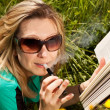 Young blond woman with electric cigarette is reading a book — Stock Photo