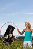 Blonde woman holding hula hoop and dog jumps through — Stock Photo