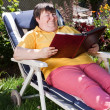 Disabled woman reading a book in the garden — Stock Photo