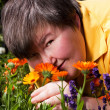 Disabled woman lying on grass and smell of flowers — Stock Photo