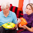 Old and young womgetting loveless gifts — Stock Photo #34007299