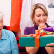 Senior woman and blonde female gets presents — Stock Photo