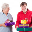 Stock Photo: Female senior and mental disabled womholding gifts