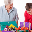 Senior with mentally handicapped woman consider gifts — Stock Photo