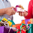 Stock Photo: Senior and daughter reaching gift to each other