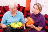 Old and young woman getting loveless gifts — Stock Photo