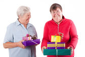 Female senior and mental disabled woman holding gifts — Stock Photo