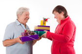 Senior and mental disabled woman holding gifts — Stock Photo