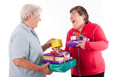 Senior and mental disabled woman holding presents — Stock Photo