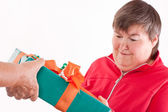 Disabled woman receives gift from senior — Stock Photo