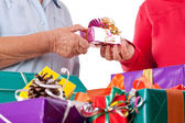 Senior and daughter reaching gift to each other — Stock Photo