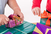 Two women wrap or unpack gifts — Stock Photo