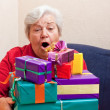 Senior sitting on the couch with gifts — Stock Photo