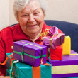 Senior sits and gets or give many gifts — Stock Photo
