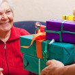 Female Senior sits and gets or give many gifts — Stock Photo