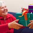 Female Senior sits and gets or give many presents — Stock Photo