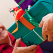 Senior sits and gets or give many presents closeup — Stock Photo