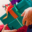 Senior sits and gets or give many gifts closeup — Stock Photo