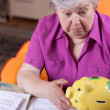 Depressed senior citizen looking for piggy bank — Stock Photo