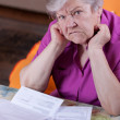 Stock Photo: Elderly womsits in front of papers and desperate