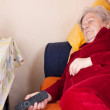 Elderly woman lying on sofa and sleeps — Stock Photo