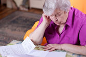Senior reads papers and works hard — Stock Photo