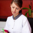 Pretty nurse makes notes to — Stock Photo #34027581