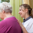 Nurse and elderly woman standing at the window — Stockfoto