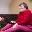 Mentally disabled woman watching television and enjoys — Stock Photo