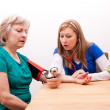 Doctor measures senior adult the blood pressure — Stock Photo