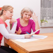 Two women pondering over documents — Stock Photo