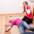 Stock Photo: Senior collapsed young womcalling help