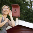 Young woman listening to bird house — Stock Photo