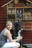 Woman with dog showing insect hotel — Stock Photo
