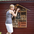 Young woman showing insect hotel — Stock Photo