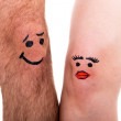 Two legs with faces, white background — Stock Photo
