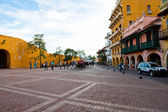 Puerto del Reloj Historic entranceway in Cartagena, Colombia. can be seen in front of the gate walking about near a statue. — Stock Photo