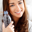 Pretty young girl holding a bottle of water and smiling — Stock Photo