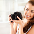 Pretty woman is a proffessional photographer with dslr camera — Stock Photo #14776601