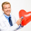 Doctor holding heart on white background — Stock Photo